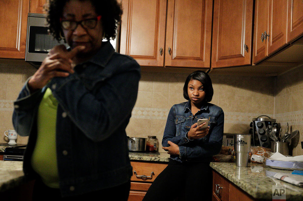 Aajah Washington, right, listens as her grandmother Edith Washington recalls being one of the first black students at Rowland's newly integrated high school in 1971 at their home in Rowland, N.C., Sunday, Oct. 29, 2017. She still remembers teachers making a big show of scrubbing their hands after they touched the black students' papers, children screaming racial slurs as they walked through the white neighborhood on their way to school. (AP Photo/David Goldman)