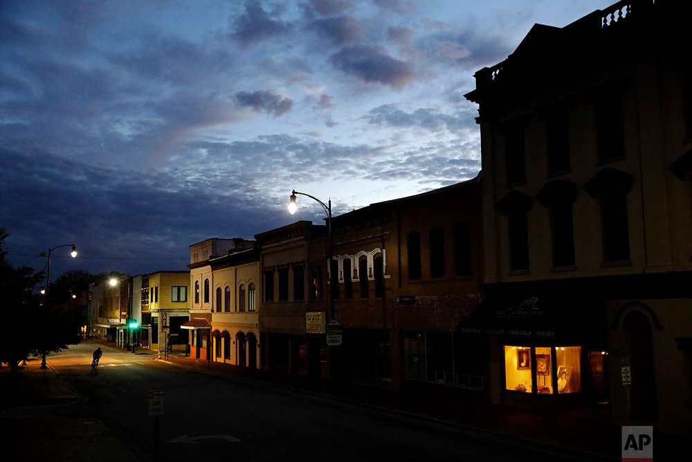 The storefront window of a portrait studio is lit up along a downtown street at dusk in Lumberton, N.C., Saturday, Oct. 28, 2017.(AP Photo/David Goldman)