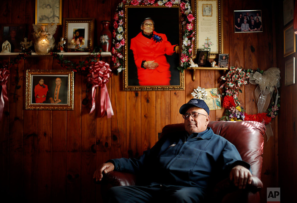 """Horace Locklear sits for a portrait under a picture of his late wife Quessie, who passed last year after 53 years of marriage, in Fairmont, N.C., Monday, Oct. 30, 2017. Locklear, a member of the Lumbee Native American tribe, says that when he was young and growing up in Robeson County he remembers having to get his food from a back window because he and his family couldn't dine in many restaurants. """"I just couldn't really understand why people couldn't get along. You know, mix and mingle."""" But he says it's gotten better over the years and he has friends of many races. While he voted for President Obama, he voted for President Trump because he thinks he can bring jobs to the region – and also, based on his reading of the Bible, because he doesn't think a woman should be president. (AP Photo/David Goldman)"""