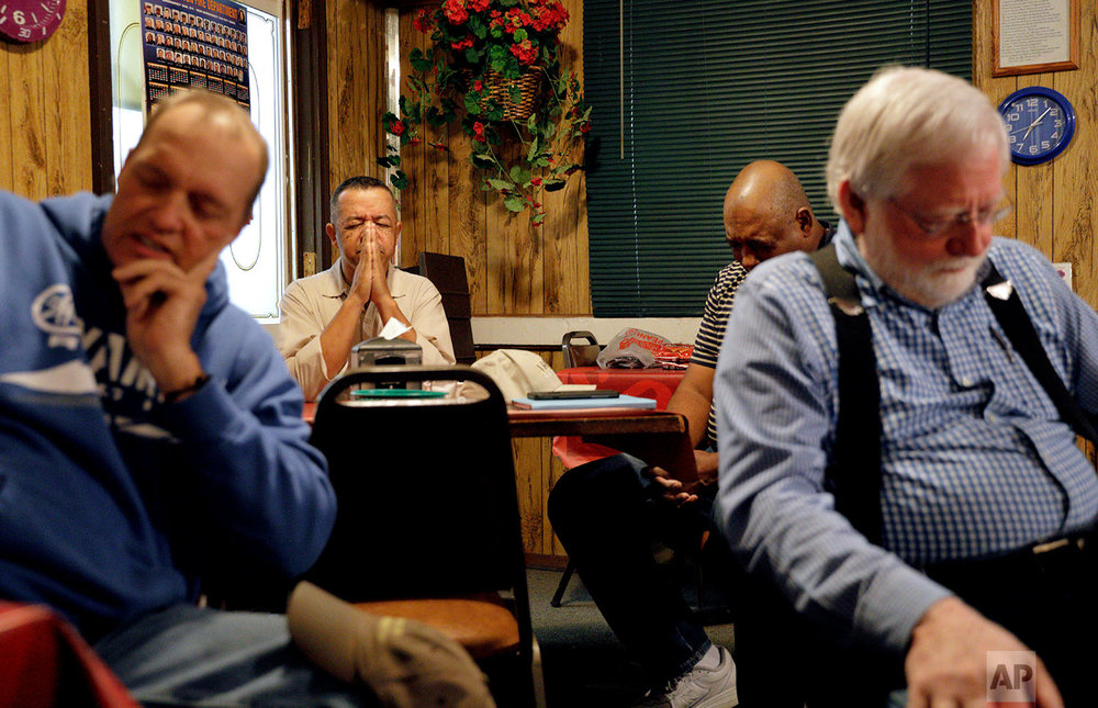 Jerry Jacobs, rear left, joins Rick Lovett, from left, Walker Davis and Jerry Batten in a prayer breakfast at a diner in Lumberton, N.C., Saturday, Oct. 28, 2017. In Robeson County, whites, blacks and Native Americans split the population - and many often remark at how well they've overcome the scars of segregation to struggle together, side by side. But churches remain largely segregated by race, and some have tried to get diverse congregations together. (AP Photo/David Goldman)