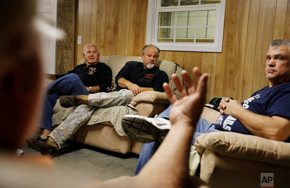 Ricky Phillips, from right, Cary Lewis and Billy Wilcox talk during their weekly dinner gathering at the home of Buddy Jones, foreground, in Lumberton, N.C., Thursday, Oct. 26, 2017. (AP Photo/David Goldman)