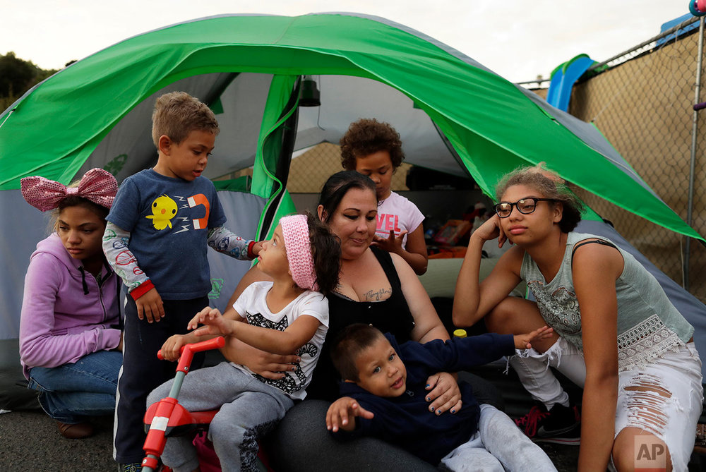 In this Nov. 8, 2017, photo, Christine Wade sits among her children in front of their donated tent in the city-sanctioned encampment on a parking lot in San Diego. They are, from left, Shawnni, 12, Roland, 4, Rayahna, 3, Jaymason, 2, Brooklyn, 8, and Shaccoya, 14. The Wade family is among several hundred people living in the city's first campground open for the homeless, set up to curb the worst Hepatitis A outbreak in the United States in decades. (AP Photo/Gregory Bull)