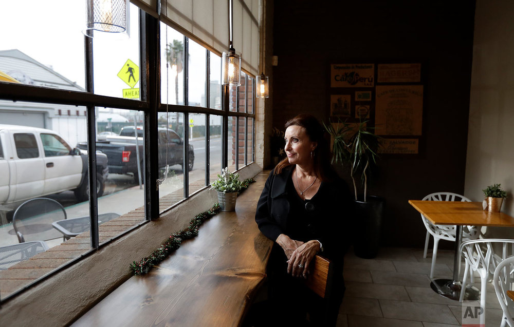 In this Nov. 28, 2017, image, Laurie Britton, owner of Cafe Virtuoso, pauses for a portrait as she works in her coffee shop in downtown San Diego. Britton has faced a deluge of problems related to the homeless population around her organic coffee roasting business. Since the city started cleaning up the streets, business has increased by 20 percent. She now welcomes the new giant tents to house the homeless - two of which will be within a block - if people end up in permanent housing. (AP Photo/Gregory Bull)