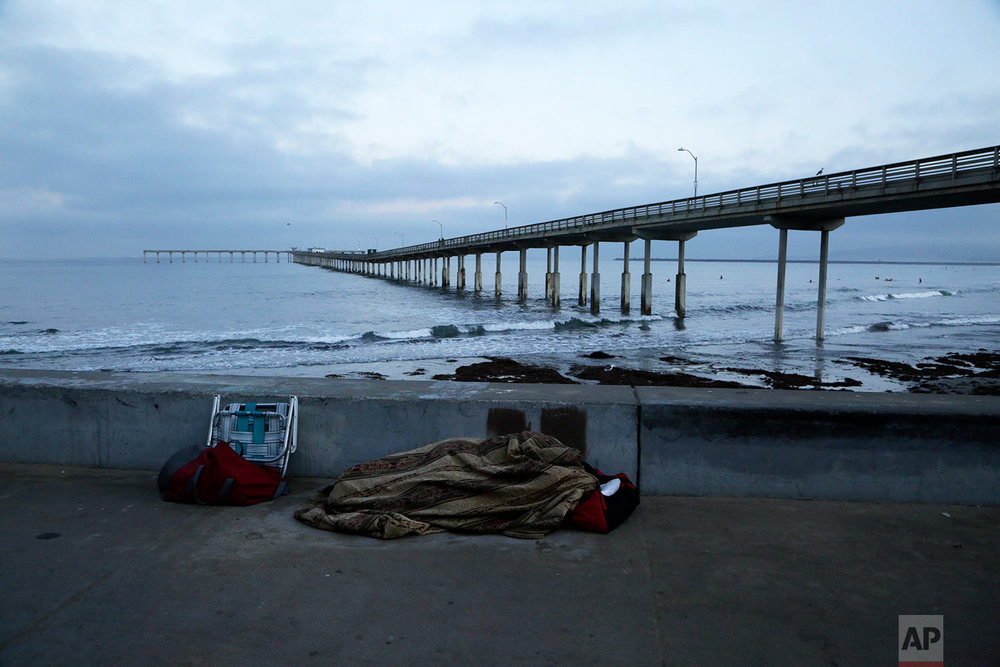 "In this Sept. 28, 2017 photo, a person sleeps under a blanket on a beach near the Ocean Beach Pier in San Diego. In a place that bills itself as ""America's Finest City,"" renowned for its sunny weather, surfing and fish tacos, spiraling real estate values have contributed to spiraling homelessness.  (AP Photo/Gregory Bull)"