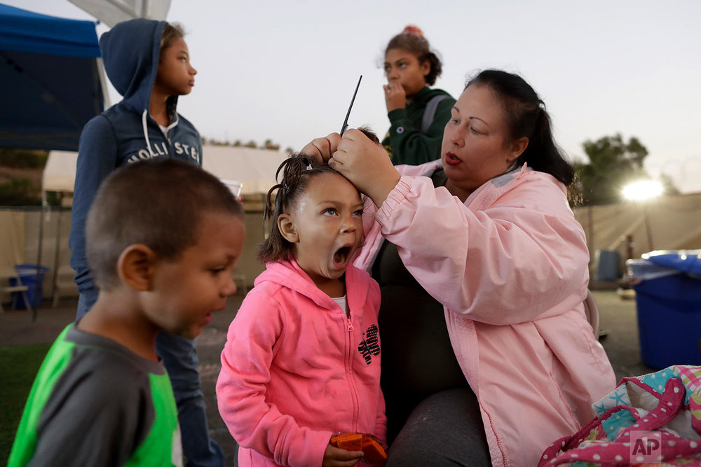 In this Oct. 26, 2017, photo, Christine Wade makes braids for Rayahna, 3, as Jaymason, 2, below left, Shawnni, 12, above left, and Shaccoya, 14, get ready to leave for school at dawn at the city-sanctioned tent encampment in San Diego. The Wade family is among several hundred people living in the city's first campground open for the homeless, set up to curb the worst Hepatitis A outbreak in the United States in decades. The new camp, in a parking lot on the edge of sprawling Balboa Park, reflects the severity of the homeless crisis gripping cities along the west coast. (AP Photo/Gregory Bull)