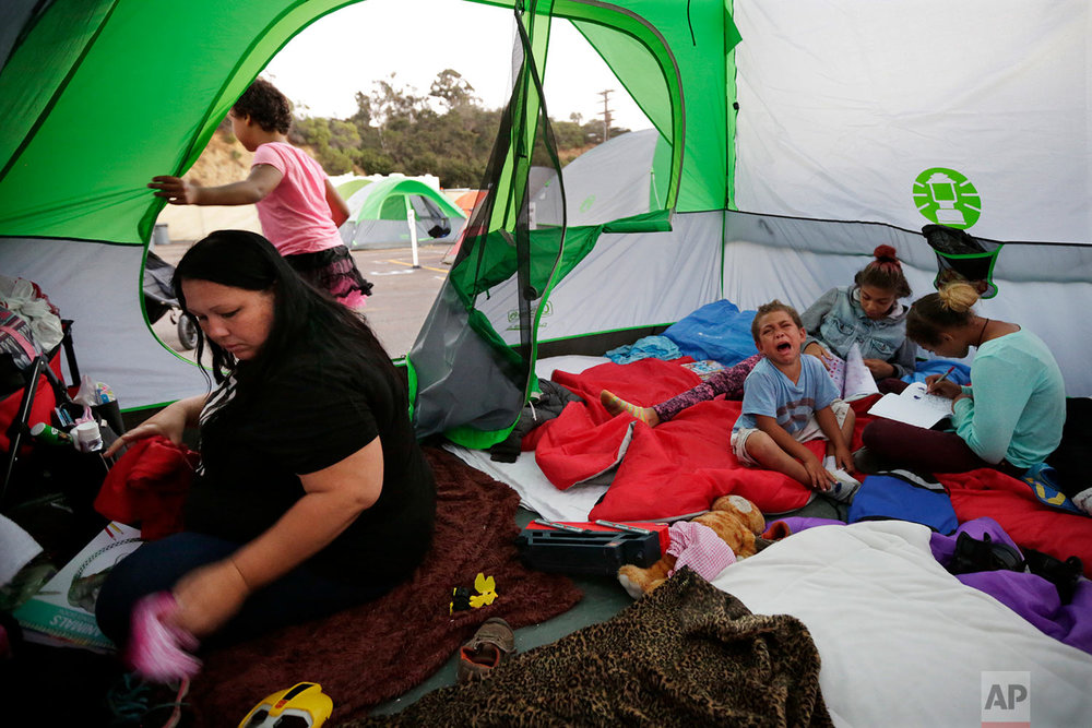 In this Oct. 18, 2017, photo, Christine Wade, left, sorts clothing as Roland, 4, cries and sisters Shawnni, 12, right, and Shaccoya, 14, draw in the family's tent provided by the city in a sanctioned encampment in San Diego. The Wade family is among several hundred people living in the city's first campground open for the homeless, set up to curb the worst Hepatitis A outbreak in the United States in decades. The new camp, in a parking lot on the edge of sprawling Balboa Park, reflects the severity of the homeless crisis gripping cities along the west coast. (AP Photo/Gregory Bull)
