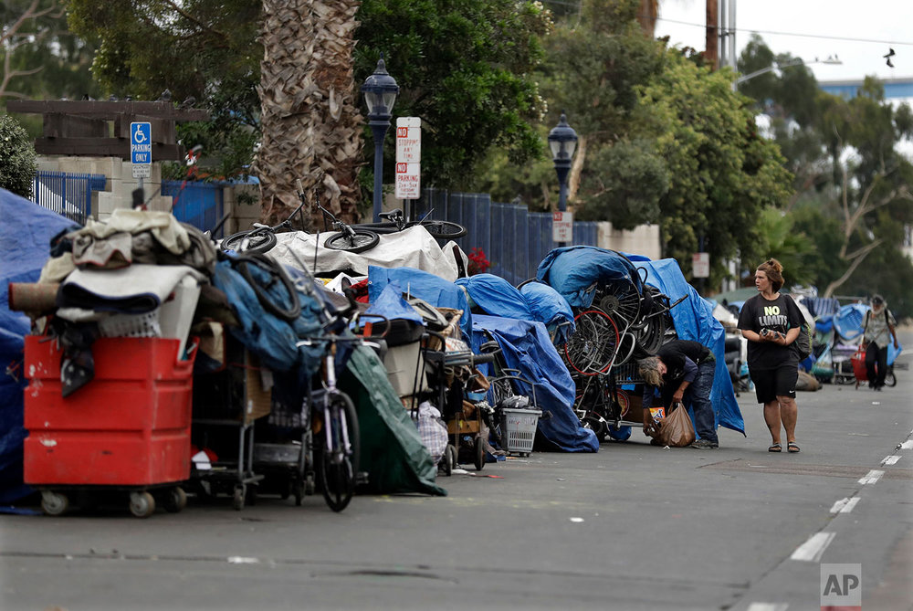 "In this Sept. 19, 2017 photo, trash from homeless encampments lines a street in San Diego. In a place that bills itself as ""America's Finest City,"" renowned for its sunny weather, surfing and fish tacos, spiraling real estate values have contributed to spiraling homelessness in San Diego. Most alarmingly, the explosive growth in the number of people living outdoors has contributed to a hepatitis A epidemic.  (AP Photo/Gregory Bull)"