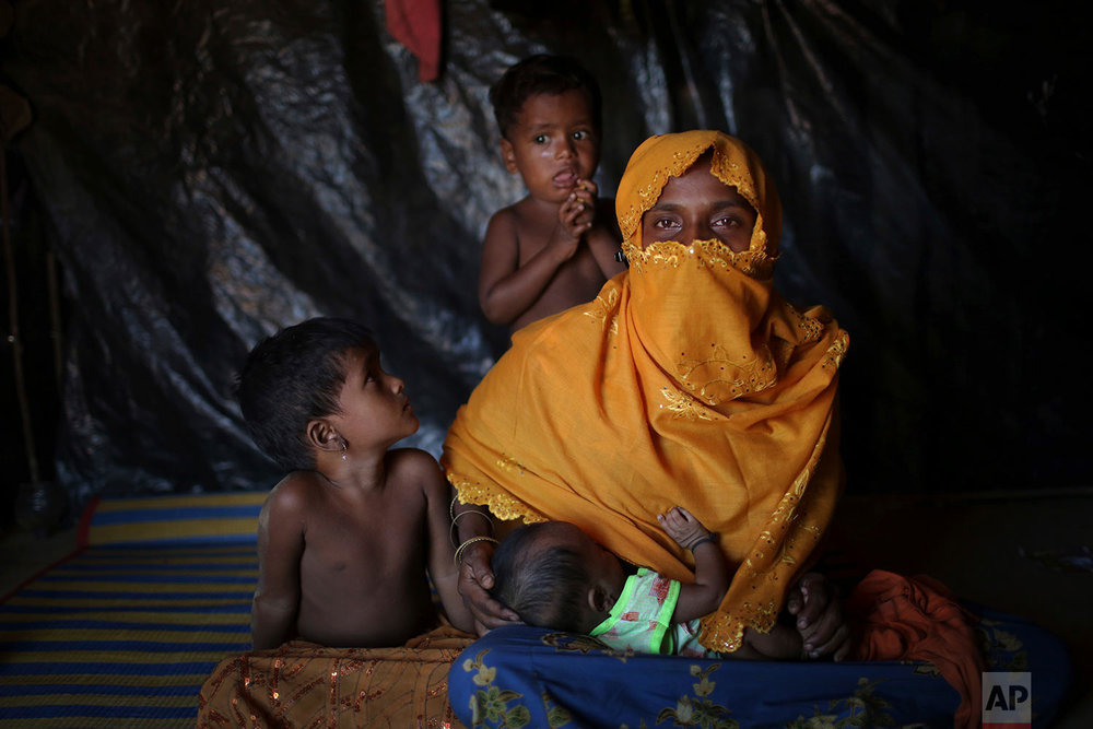 In this Sunday, Nov. 19, 2017, photo, K, 25, mother of six, who says she was raped by members of Myanmar's armed forces in late August, is photographed as she nurses her baby with her two children beside her in their tent in Kutupalong refugee camp in Bangladesh.  (AP Photo/Wong Maye-E)