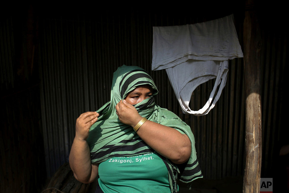 In this Wednesday, Nov. 22, 2017, photo, N, 31, mother of girl, who says she was raped by members of Myanmar's armed forces in late August, adjusts her headscarf as she is photographed outside her home in Kutupalong refugee camp in Bangladesh.  (AP Photo/Wong Maye-E)
