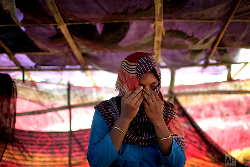 In this Monday, Nov. 20, 2017, photo, D, 30, mother of four where two of her sons are missing, who says she was raped by members of Myanmar's armed forces in late August, hides her face while she was being photographed in a friend's tent in Kutupalong refugee camp in Bangladesh.  (AP Photo/Wong Maye-E)