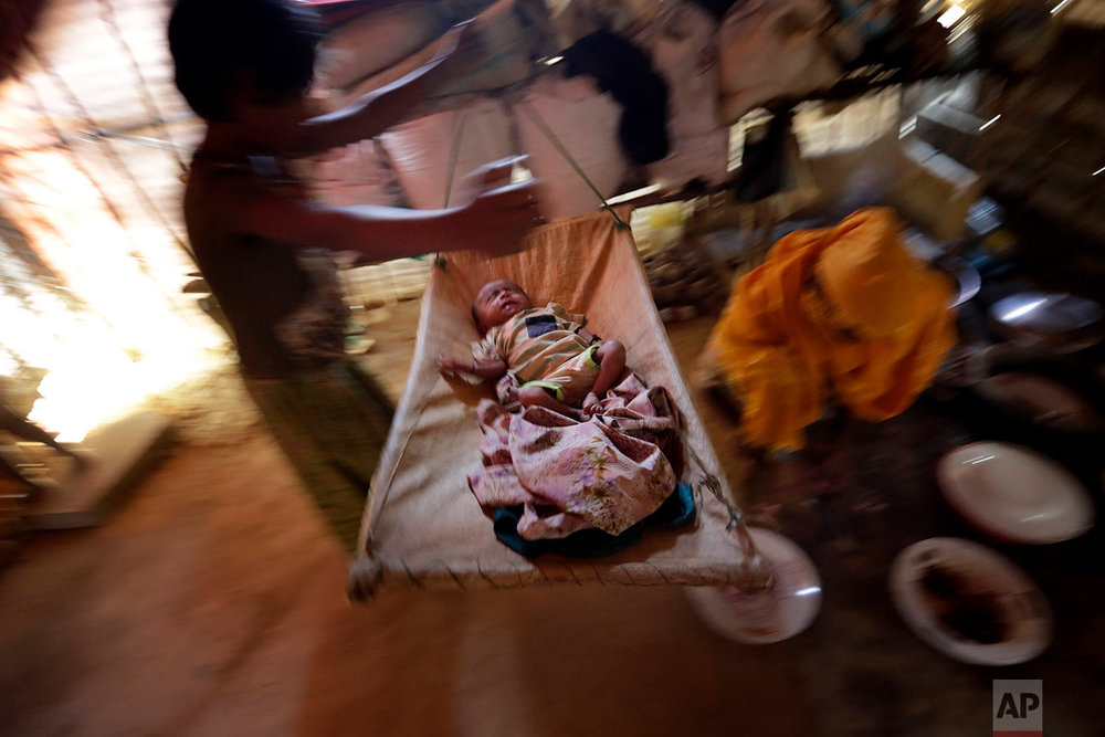 In this Tuesday, Nov. 21, 2017, photo, K, 25, right, prepares lunch while her children wait beside her in their tent in Kutupalong refugee camp in Bangladesh. (AP Photo/Wong Maye-E)