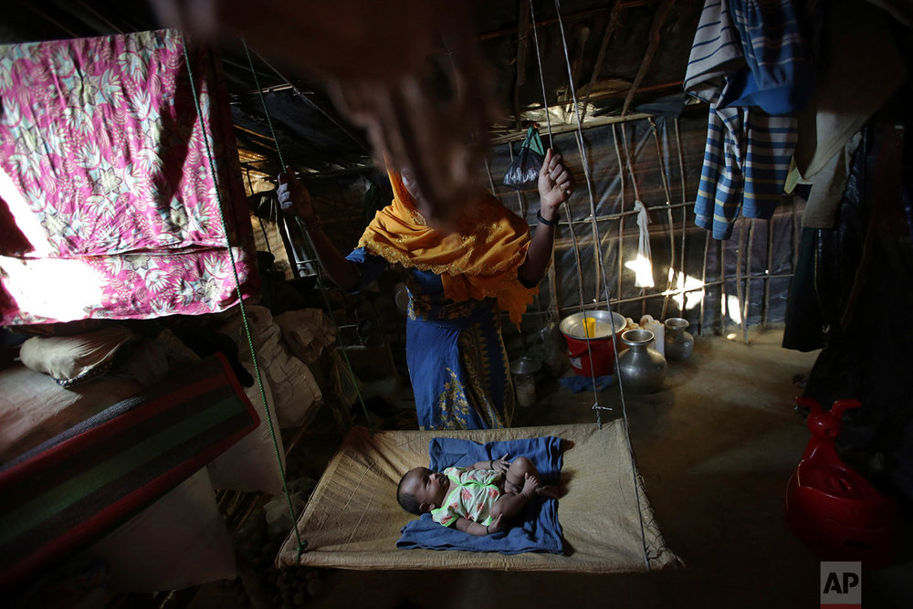 In this Sunday, Nov. 19, 2017, photo, K, 25, swings her two month old baby in her tent in Kutupalong refugee camp in Bangladesh. (AP Photo/Wong Maye-E)