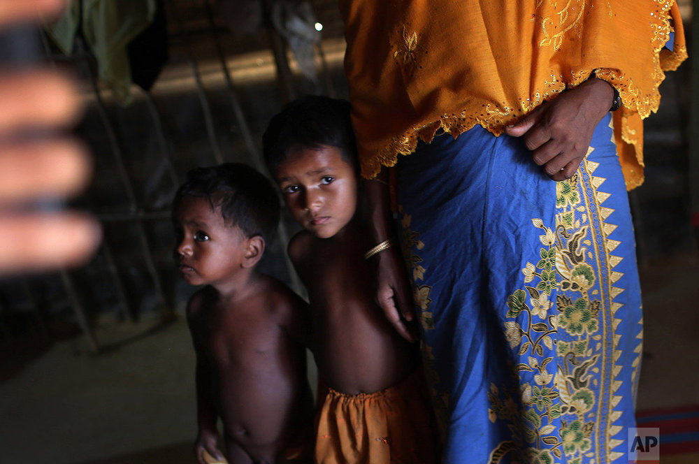 In this Sunday, Nov. 19, 2017, photo, K, 25, right, speaks to The Associated Press while her children watch cautiously beside her in their tent in Kutupalong refugee camp in Bangladesh. (AP Photo/Wong Maye-E)