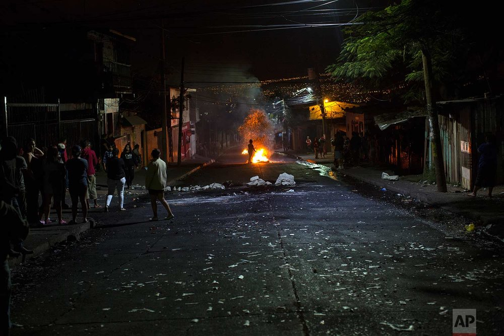 Anti-government protestors gather around barricades in protest during a government imposed dawn-to-dusk curfew in Tegucigalpa, Honduras, Sunday, Dec. 3, 2017. (AP Photo/Rodrigo Abd)