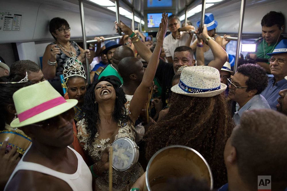 People dance and sing in the Samba Train in Rio de Janeiro, Brazil, Saturday, Dec. 2, 2017. Hundreds of people have gathered at Rio de Janeiro's main train station for Brazil's annual Samba Day festivities. (AP Photo/Leo Correa)