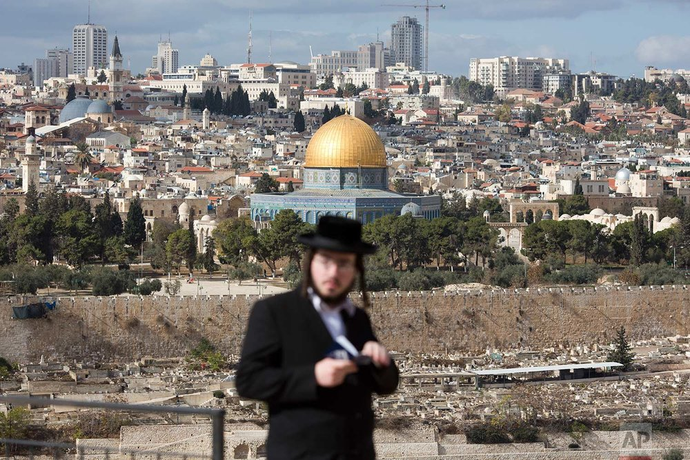 An orthodox Jewish man reads from a holy book in a cemetery near the Dome of the Rock Mosque in the Al Aqsa Mosque compound in Jerusalem's Old City, Thursday, Dec. 7, 2017. A day earlier, U.S. President Donald Trump announced his decision to recognize Jerusalem as Israel's capital. (AP Photo/Ariel Schalit)