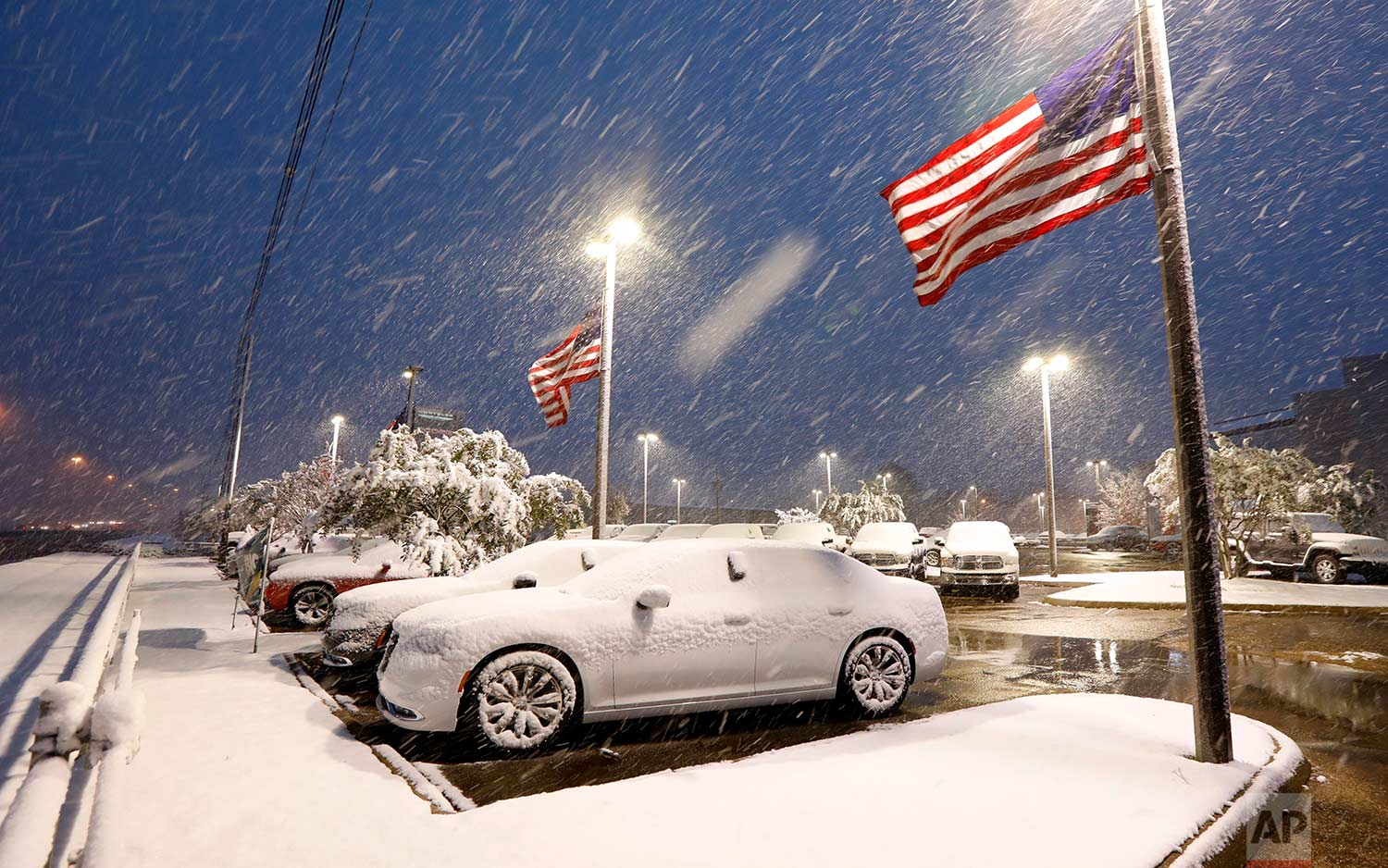 U.S. flags wave as snow falls, blanketing vehicles in a car sales lot, Friday, Dec. 8, 2017, in Jackson, Miss. (AP Photo/Rogelio V. Solis)
