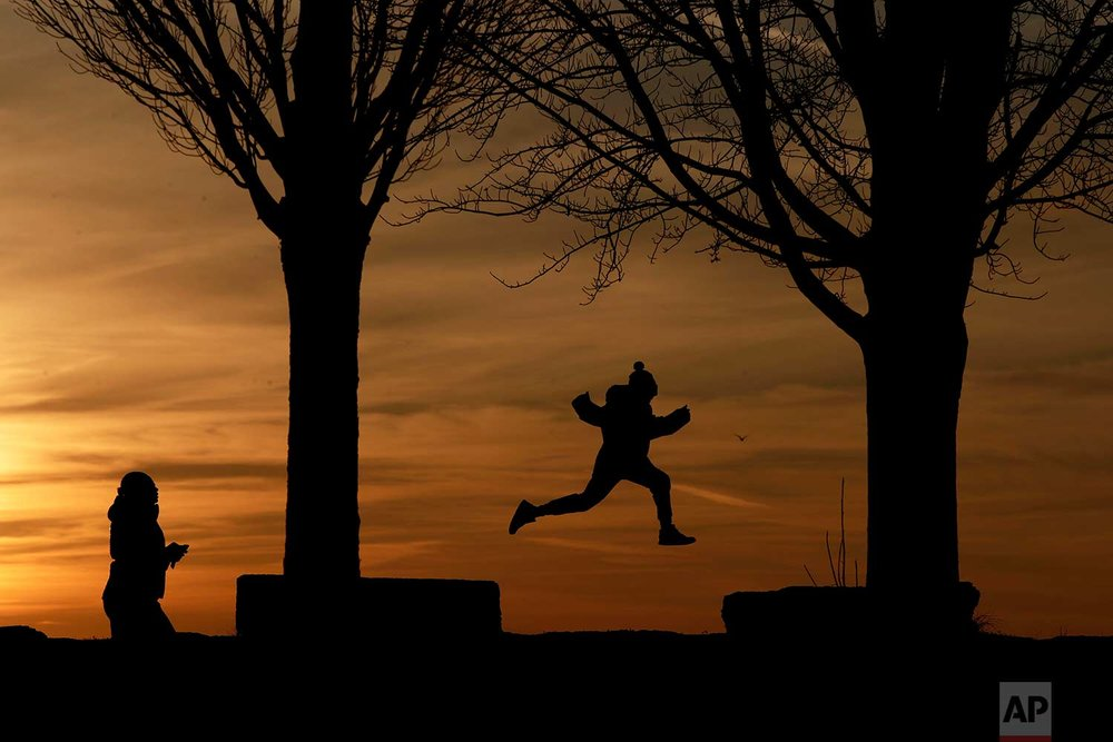 A child leaps between rock platforms as the sun sets behind Lake Erie at the Erie Basin Marina, Saturday, Dec. 2, 2017, in Buffalo, N.Y. (AP Photo/Julio Cortez)