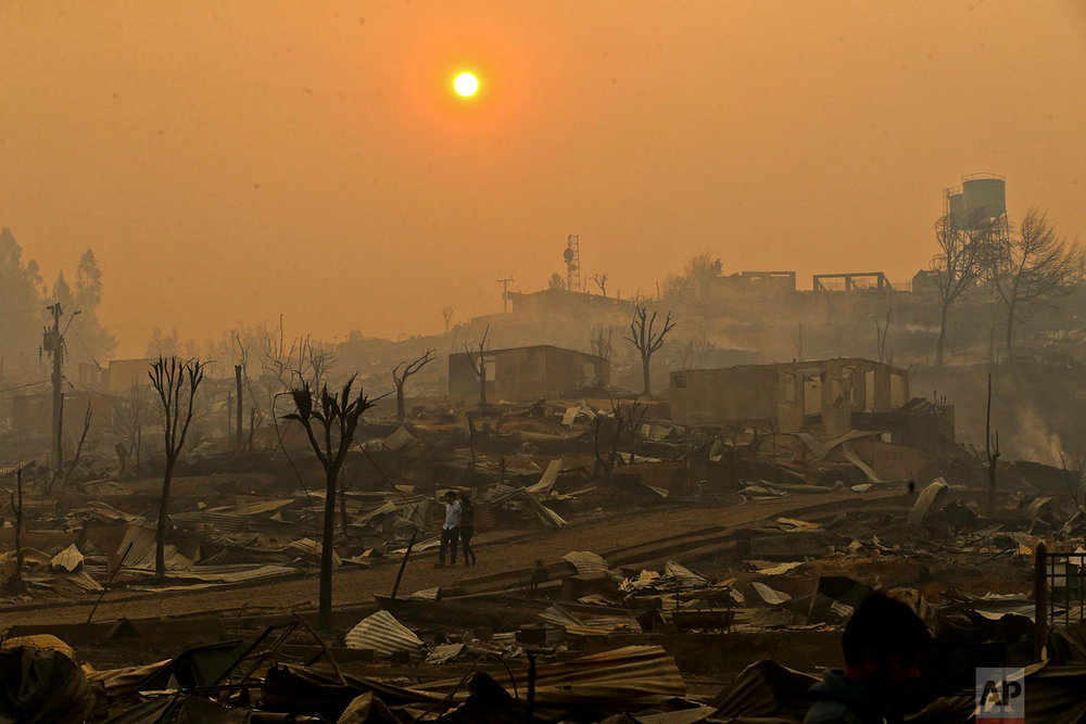 A couple walks through a neighborhood destroyed by wildfires in Chile's Santa Olga community, Thursday, Jan. 26, 2017. The town was consumed by the country's worst wildfires, engulfing the post office, a kindergarten and hundreds of homes. (AP Photo/Esteban Felix)
