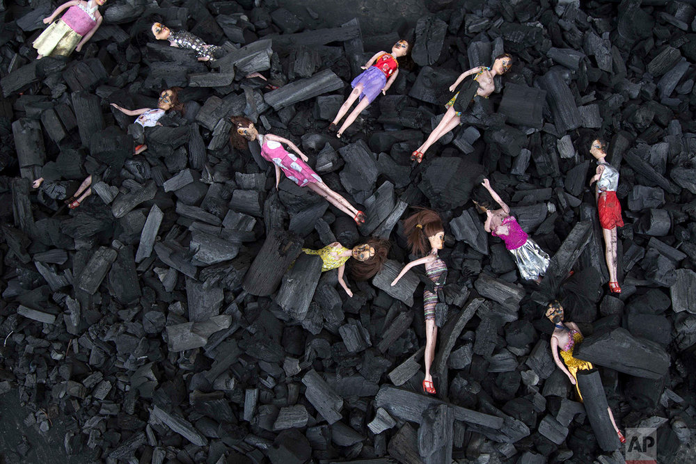 Charred-stained dolls placed on a bed of charcoal are part of artists' installation placed at the front gate of presidential house in remembrance of the victims of a fire at a girls' home in Guatemala City, Thursday, March 9, 2017. About 700 children lived in the Virgen de la Asunción Safe Home with a maximum capacity for 500. Some dormitories housed more than twice the number of children authorized for the space. (AP Photo/Luis Soto)