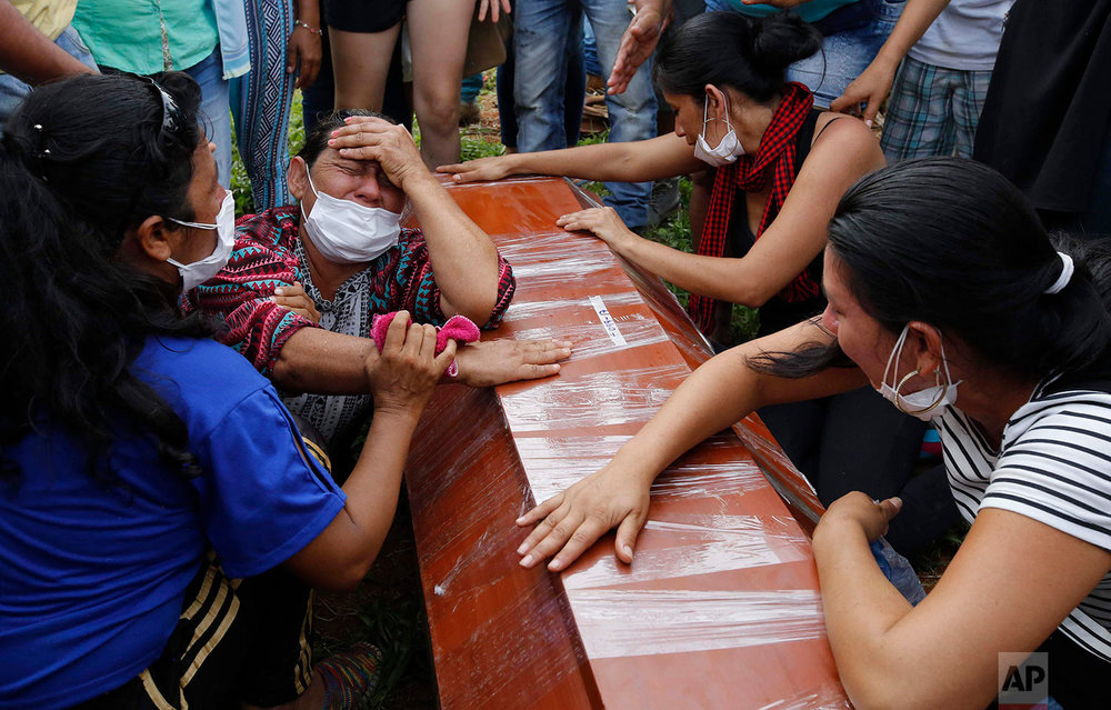 Women cry over the coffin of a relative who died in an avalanche during heavy rains, during a mass burial in Mocoa, Colombia, Monday, April 3, 2017. Rivers sent an avalanche of floodwaters, mud and debris through the small city, killing more than 260 people and leaving many more injured and homeless. (AP Photo/Fernando Vergara)