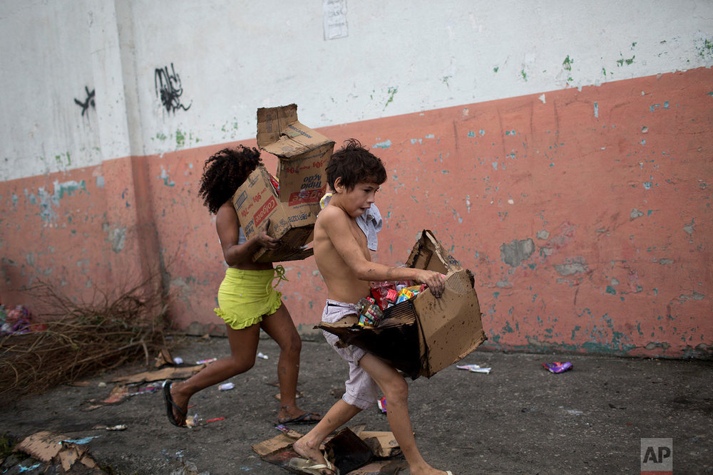 Children run off with boxes they filled with merchandise salvaged from a cargo truck allegedly set on fire by drug traffickers in Rio de Janeiro, Brazil, Tuesday, May 2, 2017. Several public buses and cargo trucks were torched in what military police said was likely gang retaliation for a large anti-drug operation. (AP Photo/Silvia Izquierdo)