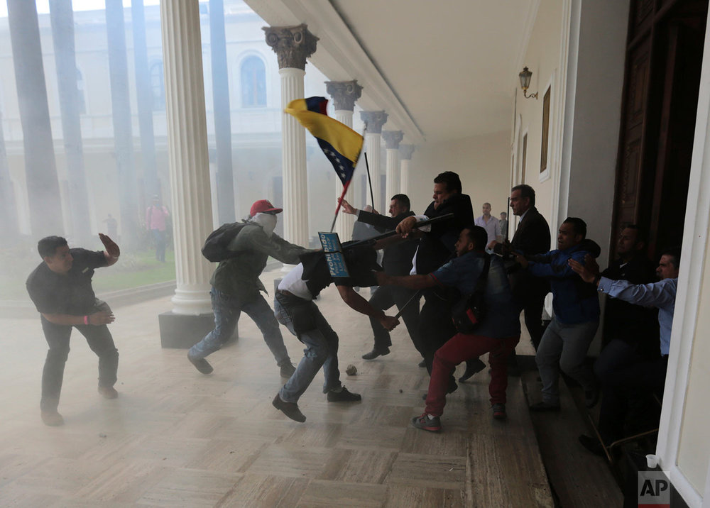 Opposition lawmakers brawl with pro-government militias trying to force their way into the National Assembly during a special session coinciding with Venezuela's independence day, in Caracas, Wednesday, July 5, 2017. At least five lawmakers were injured in the attack which came after the election of a pro-government constitutional assembly now ruling with virtually unlimited powers. (AP Photos/Fernando Llano)