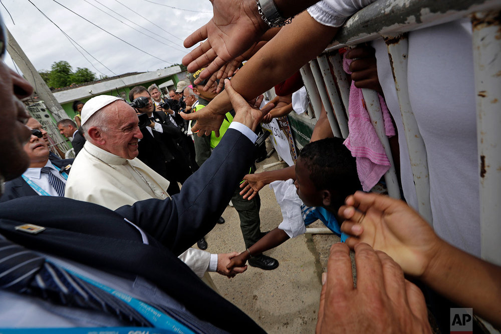 Pope Francis' greets people in the San Francisco neighborhood of Cartagena, Colombia, Sunday, Sept. 10, 2017. The Argentine pontiff is in the port city to honor St. Peter Claver, a 17th-century Jesuit who ministered to the tens of thousands of African slaves who arrived to be sold. (AP Photo/Andrew Medichini)