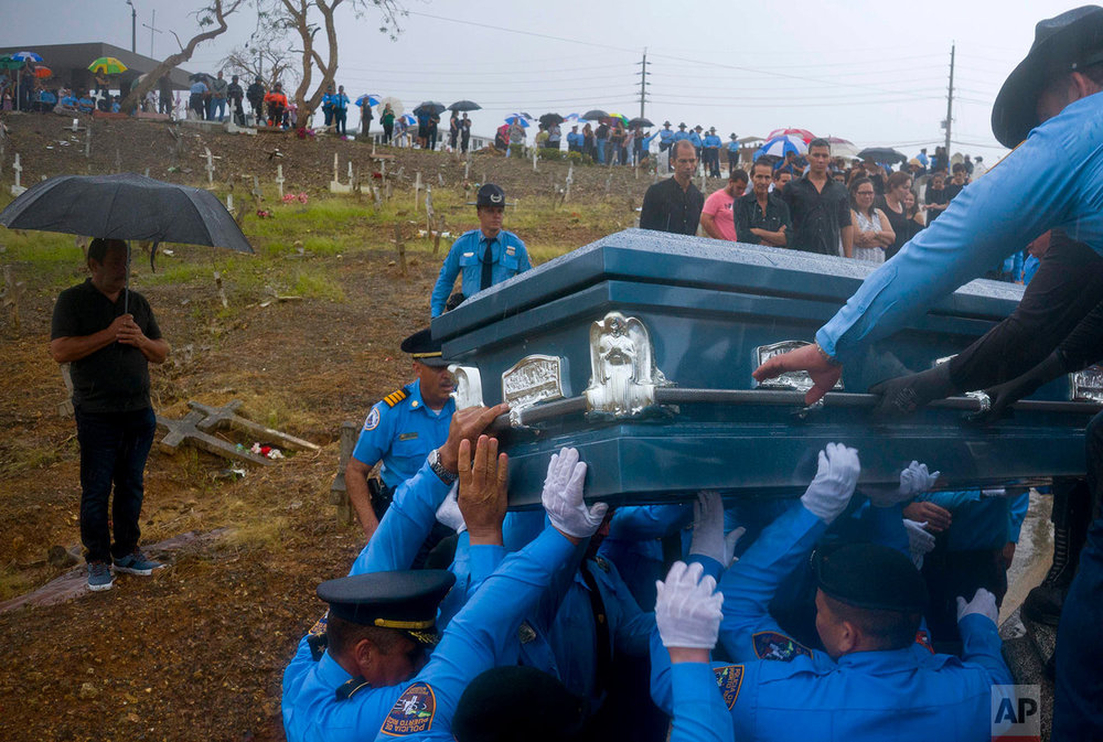 Police lift the coffin of fellow officer Luis Angel Gonzalez Lorenzo, who was killed while trying to cross a river in his car during the passage of Hurricane Maria, as they bury him in Aguada, Puerto Rico, Friday, Sept. 29, 2017. The Category 4 storm destroyed tens of thousands of homes and killed at least 55 people across the U.S. territory. (AP Photo/Ramon Espinosa)
