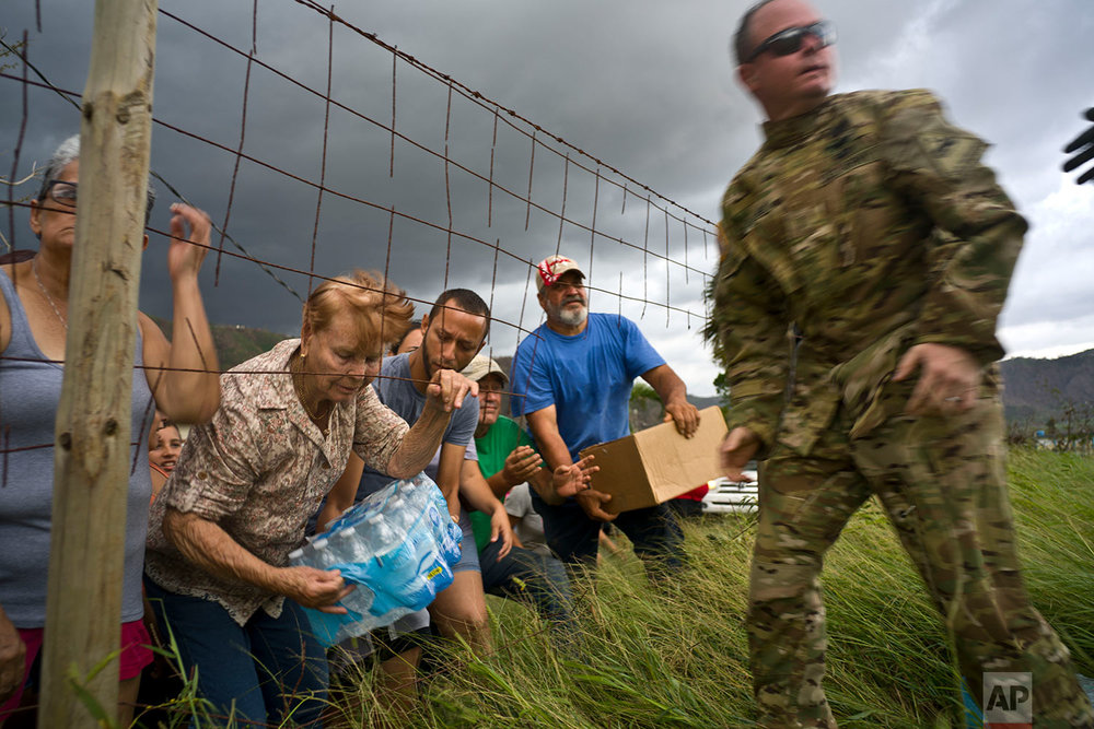 A member of the Puerto Rican National Guard delivers food and water brought via helicopter to victims of Hurricane Maria, to the  San Lorenzo neighborhood of Morovis, Puerto Rico, Saturday, Oct. 7, 2017. Puerto Rico could face more than a decade of further economic stagnation and a steep drop in population as a result of Hurricane Maria, experts say. (AP Photo/Ramon Espinosa)