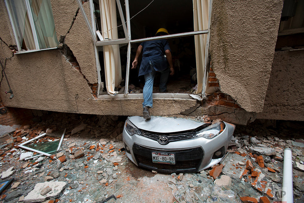 Rodrigo Diaz Mejia climbs over a crushed car into what was a second-story apartment at 517 Tokio street, felled by the earthquake almost one month prior in the Portales Norte neighborhood of Mexico City, Wednesday, Oct. 18, 2017. The 38-year-old mechanic who lives nearby said he ran to help rescue people trapped atop the buildings roofs on the day of the quake, Sept. 19, and has since been making risky trips into the ruptured structures to retrieve valuable possessions for displaced residents. (AP Photo/Rebecca Blackwell)