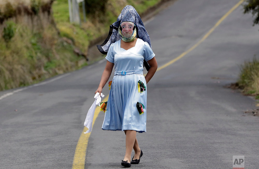 "A woman dressed for la ""La Diablada"" festival walks down a road in Pillaro, Ecuador, Friday, Jan. 6, 2017. Local legend holds that anyone who adopts a costume for the celebration and wears it at the event six years in a row will have good luck. (AP Photo/Dolores Ochoa)"