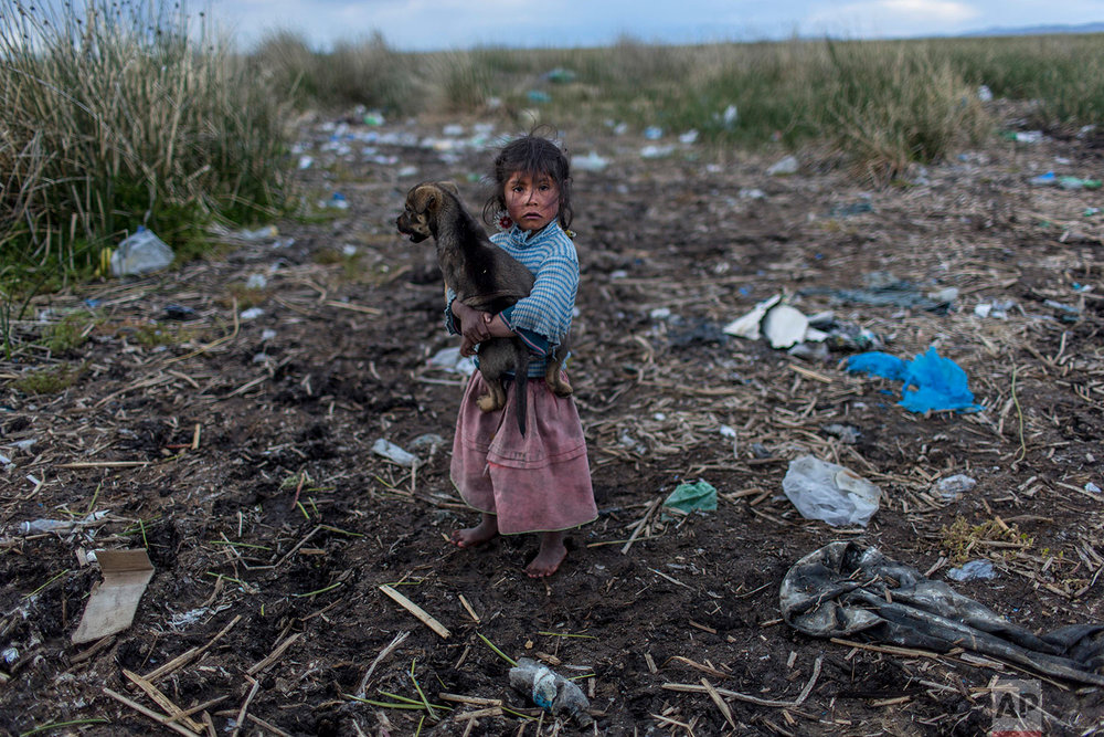 Melinda Quispe walks on the trash strewn shore of Lake Titicaca, holding her dog in her village Kapi Cruz Grande in Peru's Puno region, Saturday, Feb. 4, 2017. The governments of Peru and Bolivia signed a pact in January to spend more than $500 million to attack the pollution problem of Lake Titicaca, though the details were vague. (AP Photo/Rodrigo Abd)