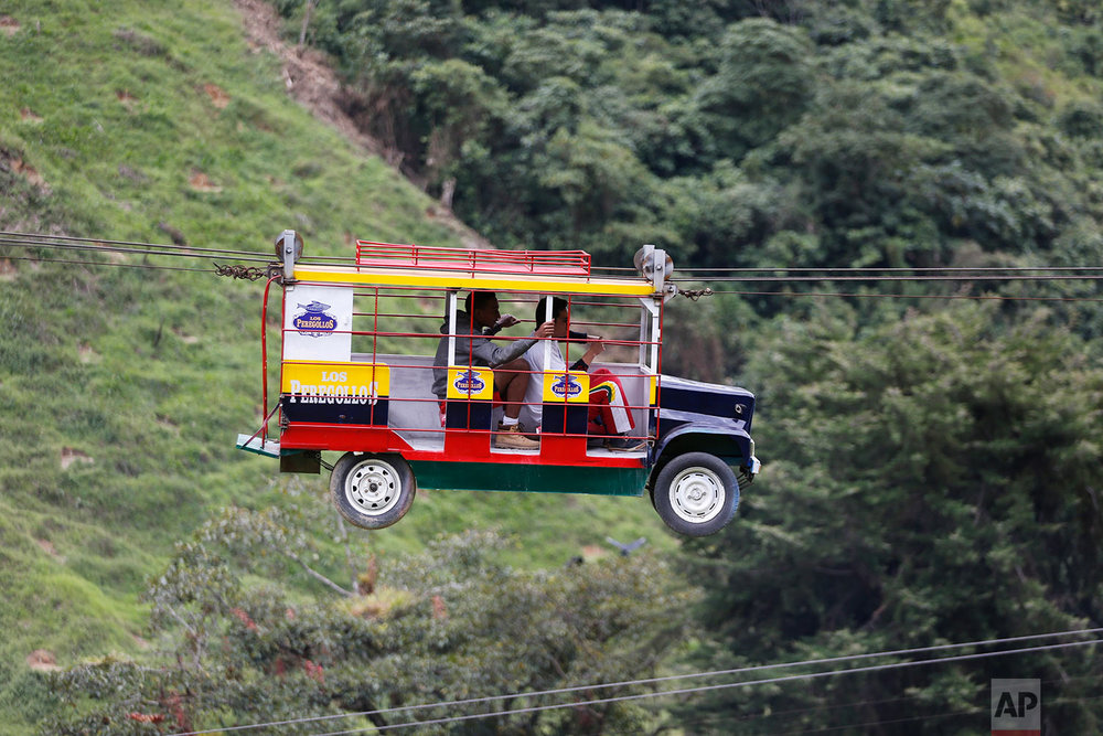 "Tourists ride a cable car in the form a of a Chiva, a bus used to serve rural routes, in Pitalito, Colombia, Tuesday, April 5, 2017. The ride called ""La Chiva Voladora"" costs about $0.70 and you zip along about 800 meters from one side of a hill to another. (AP Photo/Fernando Vergara)"