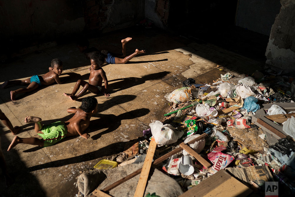 Children slide on a puddle near trash as they play in a squatter building that used to house the Brazilian Institute of Geography and Statistics (IBGE) in the Mangueira slum of Rio de Janeiro, Brazil, Sunday, Sept. 10, 2017. Toddlers roam in the abandoned building where mounds of trash create pockets of stench. (AP Photo/Felipe Dana)