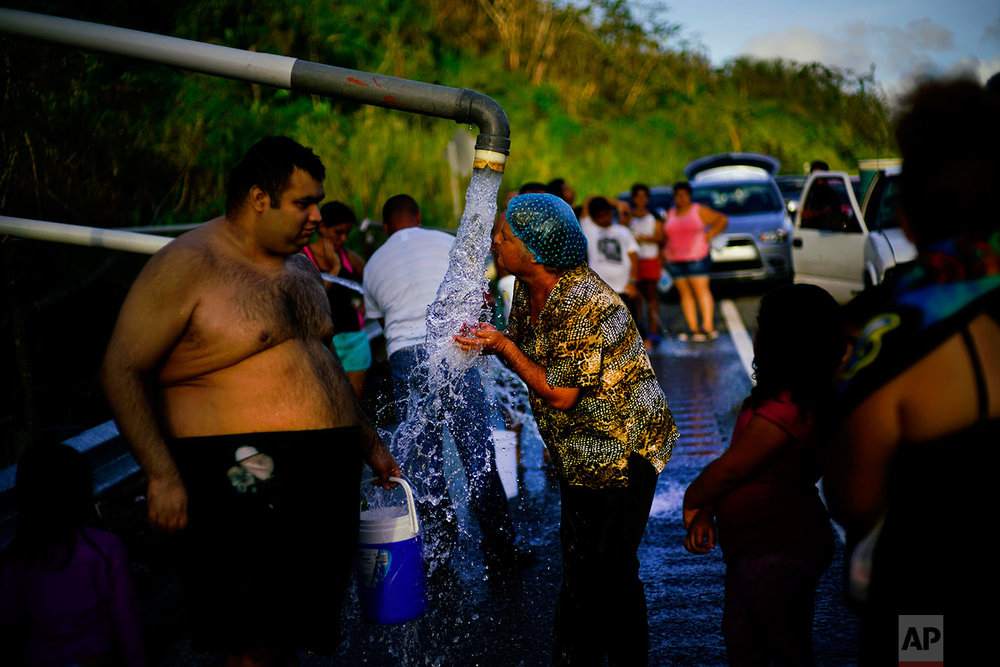 People who lost access to water in the wake of Hurricane Maria gather at pipes carrying water from a mountain creek, on the side of the road in Utuado, Puerto Rico, Saturday, Oct. 14, 2017. Nearly 10 percent of people were still without water almost two months after the storm. (AP Photo/Ramon Espinosa)
