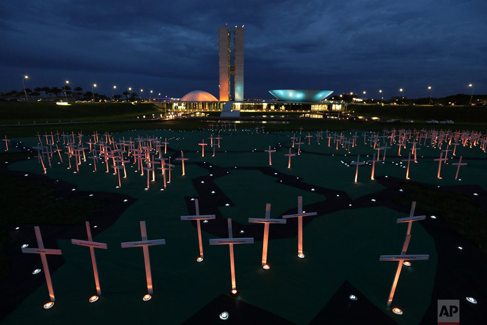 "Crosses depicting people murdered for defending the forest stand on a large map of the Amazon, during a protest against the illegal timber trade, in front of the Brazilian National Congress building, in Brasilia, Brazil, Tuesday, Nov. 21, 2017. Greenpeace Brazil released the report ""Blood-Stained Timber - Rural Violence and the Theft of Amazon Timber,"" alerting that the U.S., Germany, France, Netherlands, Denmark, Italy, Belgium and Japan imported timber from a Brazilian sawmill linked to a massacre in a remote area of Mato Grosso State, in Colniza, that took place last April 19. (AP Photo/Eraldo Peres)"