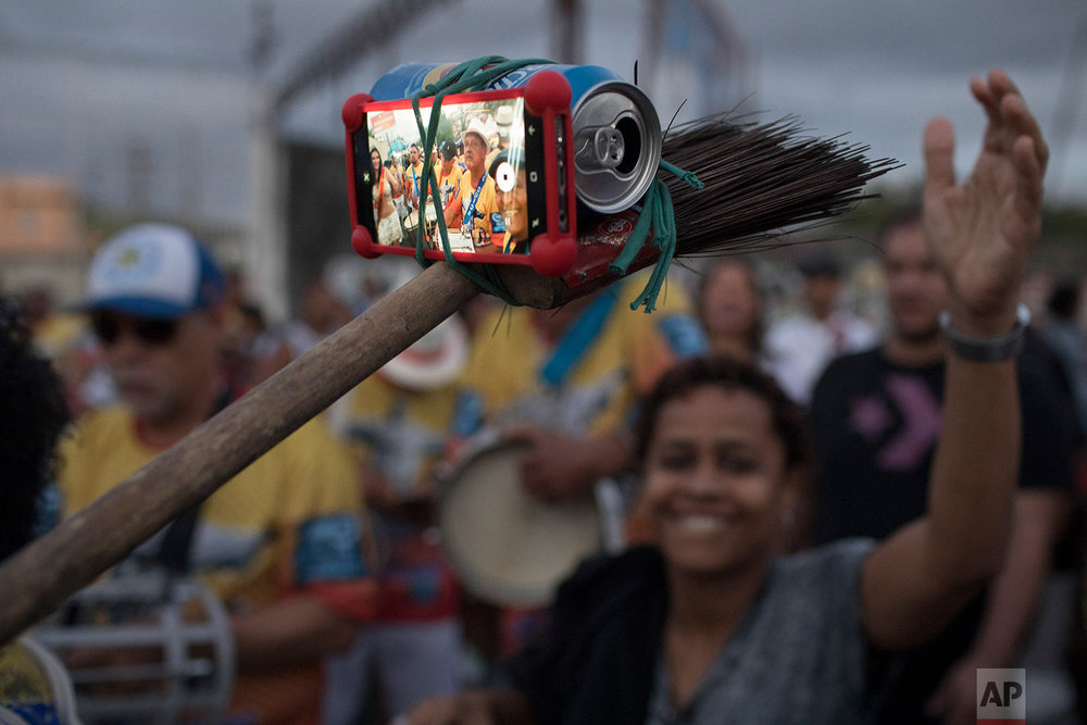A samba band member turns a broom, beer can and rubber band into a selfie stick at the Oswaldo Cruz neighborhood, marking Samba Day in Rio de Janeiro, Brazil, Saturday, Dec. 2, 2017. The Samba Train is made up of several normal commuter metro trains filled with Samba musicians to transport revelers to the Oswaldo Cruz neighborhood for music shows, all in commemoration of National Samba Day. (AP Photo/Leo Correa)