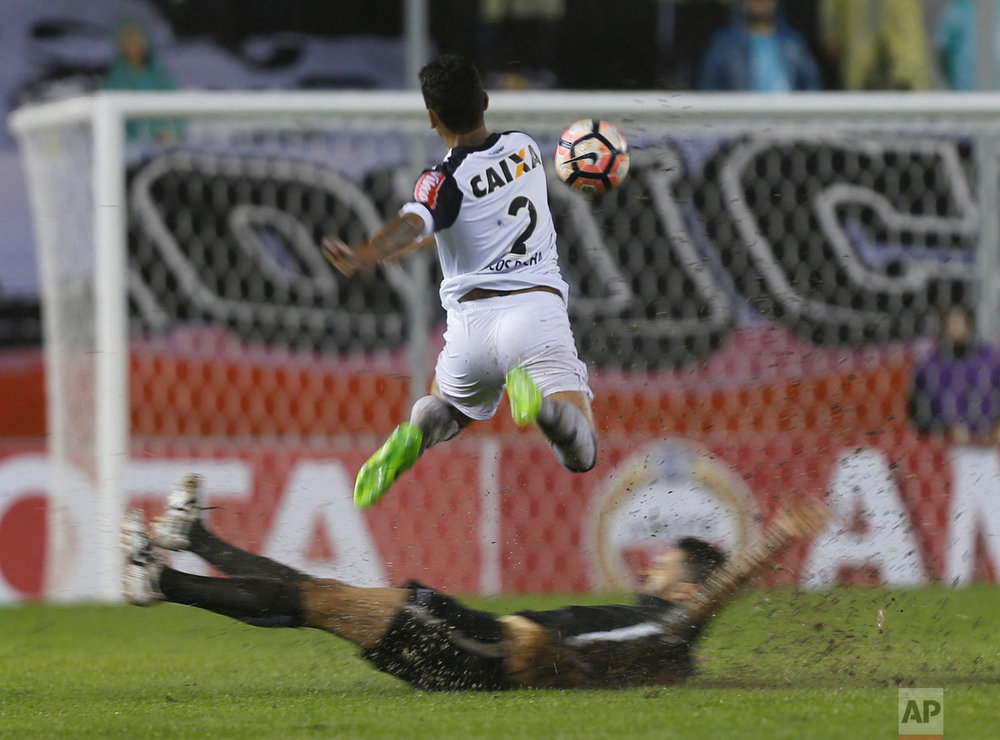 Marcos Rocha, top, of Brazil's Atletico Mineiro, fights for the ball with Santiago Salcedo, of Paraguay's Libertad, during a Copa Libertadores soccer match in Asuncion, Paraguay, Wednesday, April 19, 2017. (AP Photo/Jorge Saenz)
