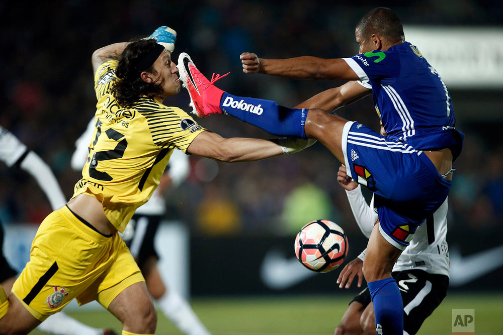 Cassio, goalkeeper of Brazil's Corinthians, left, fights for the ball with Leandro Benegas, of Universidad de Chile during a Copa Sudamericana soccer match in Santiago, Chile, Wednesday, May 10, 2017. (AP Photo/Luis Hidalgo)
