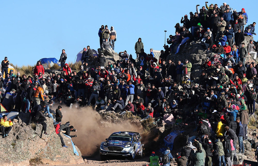 A crowd watches drivers Ott Tanak and Jarveoja Martin, from Estonia, race their Ford Fiesta WRC during the FIA World Rally Championship in El Condor, Cordoba, Argentina, Sunday, April 30, 2017. (AP Photo/Nicolas Aguilera)