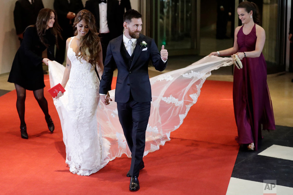 Newlywed Lionel Messi flashes a thumbs up as he and his bride Antonella Roccuzzo walk on a red carpet to pose for photographers after tying the knot in a civil ceremony in Rosario, Argentina, Friday, June 30, 2017. Guests including teammates and former teammates of the Barcelona star attended the highly anticipated ceremony. (AP Photo/Victor R. Caivano)
