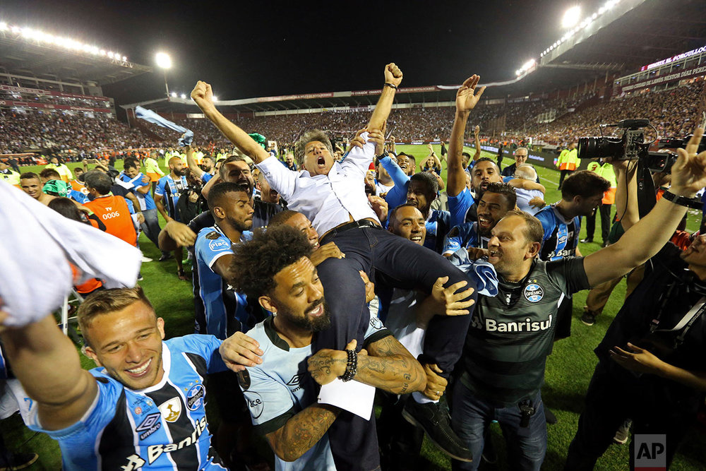 Brazil's Gremio soccer players carry their coach Renato Gaucho after winning the Copa Libertadores championship following their game against Argentina's Lanus in Buenos Aires, Argentina, Wednesday, Nov. 29, 2017. (AP Photo/Esteban Felix)