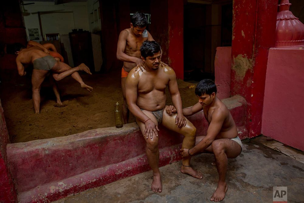 In this Nov. 20, 2017 photo, Indian Kushti wrestlers apply oil as they give a massage to a fellow wrestler, during their daily training at an akhada, a kind of wrestling hostel at Sabzi Mandi, in New Delhi, India. (AP Photo/Dar Yasin)