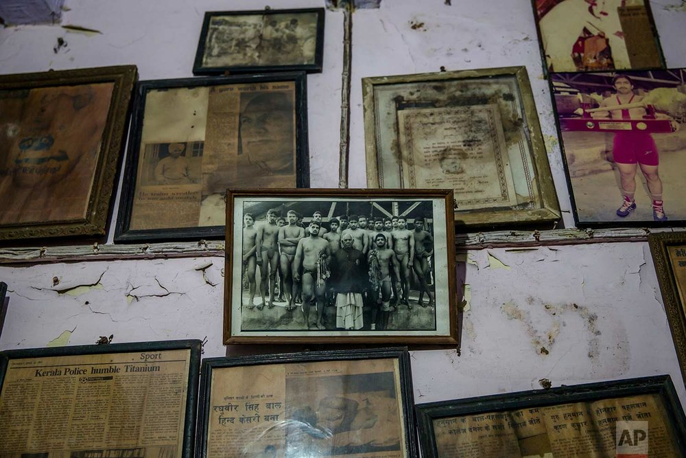 In this Nov. 20, 2017 photo, photographs and certificates belonging to Indian Kushti wrestlers are displayed on the wall of Guru Hunuman Akhada, one of India's oldest akhada at Sabzi Mandi, in New Delhi, India. (AP Photo/Dar Yasin)