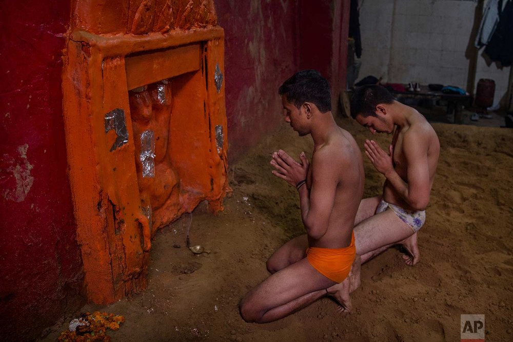 In this Nov. 27, 2017 photo, Indian Kushti wrestlers pray near a temple of Hindu god Hanuman, inside the ring, before starting their daily training at an akhada, a kind of wrestling hostel at Sabzi Mandi, in New Delhi, India. Akhadas come with shrines to the Hindu god Hanuman, who is seen as a kind of patron saint to the sport. (AP Photo/Dar Yasin)