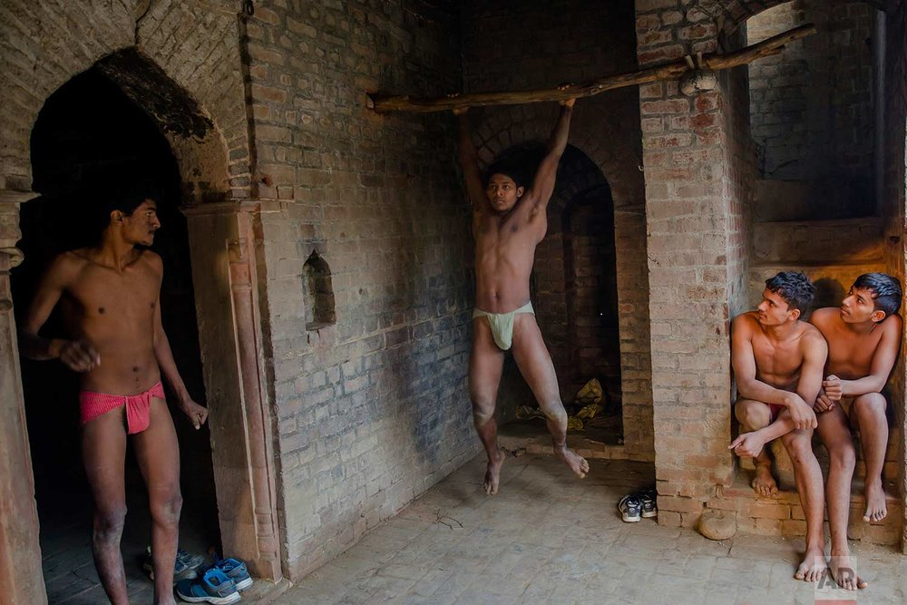 In this Nov. 22, 2017 photo, Indian Kushti wrestlers warm up during their daily training, at an akhada, a kind of wrestling hostel at Bahadurgarh, in Haryana, India. (AP Photo/Dar Yasin)