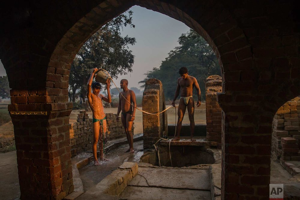 In this Nov. 22, 2017 photo, an Indian Kushti wrestler bathes near a well as others wait their turn after their daily training at an akhada, a kind of wrestling hostel at Bahadurgarh, in Haryana, India. (AP Photo/Dar Yasin)
