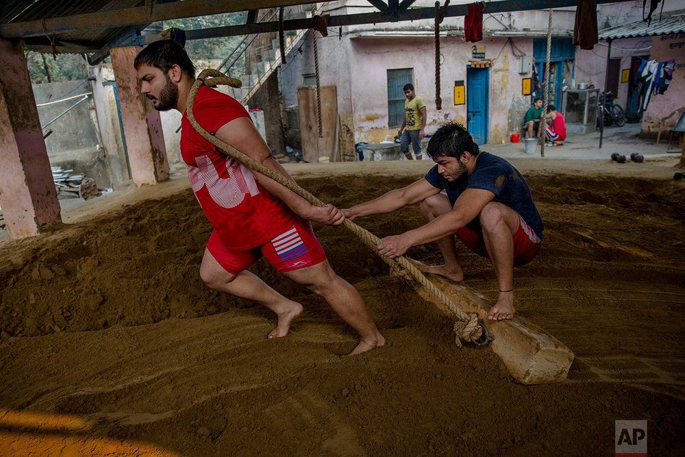 In this Nov. 20, 2017 photo, Indian kushti wrestlers prepare the ground in the ring for a training session, at Hanuman Akhada, one of India's oldest akhada at Sabzi Mandi, in New Delhi, India. (AP Photo/Dar Yasin)