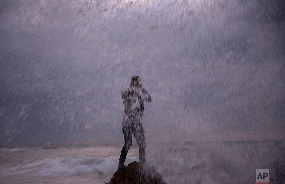 A youth stands on a rock as waves crash on the Mediterranean Sea shore during cold, stormy weather in Gaza City, Tuesday, Nov. 21, 2017. (AP Photo/Adel Hana)